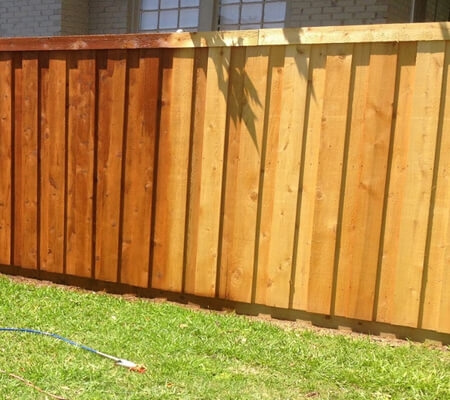 fence treatment being applied