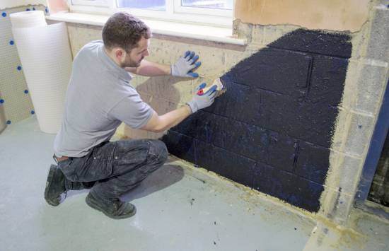 applying damp proof paint to wall