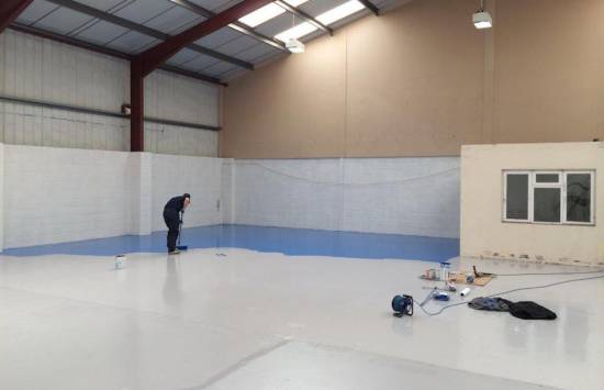 applying epoxy flooring in warehouse