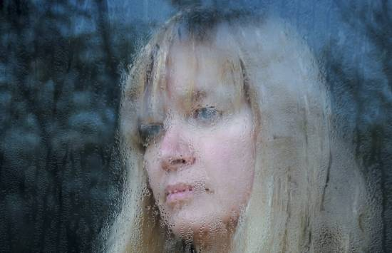 condensation on inside of a window with woman looking out