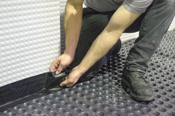 Applying corner strip to basement membrane